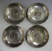 A group of four Hong Kong sterling silver circular dishes, each inset with a one dollar coin, two