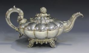 A William IV silver teapot of compressed melon form with scroll moulded spout and handle, the hinged