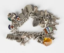 A silver curblink charm bracelet, fitted with a variety of mostly silver charms, including the