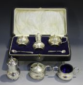 A George V silver three-piece condiment set of faceted baluster form, comprising salt, pepper caster
