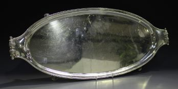A George VI silver oval tray with beaded rim and leaf scroll handles, raised on scroll feet,