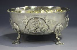 A Victorian silver circular bowl, decorated in relief with floral panels, raised on scroll legs