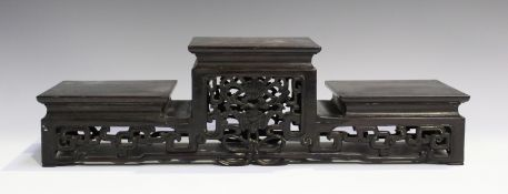 A Chinese hardwood three-tier stand, late Qing dynasty, of rectangular form, the raised central