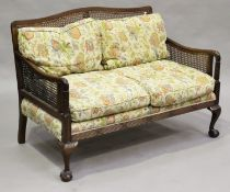 An early 20th century mahogany three-piece bergère suite, fitted with floral machined tapestry