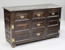 A mid-18th century oak dresser base, the moulded top above three drawers, two dummy drawers and