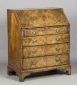 A George I walnut bureau with feather banded borders, the fall-flap enclosing a fitted interior,