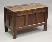 A late 17th century oak panelled coffer, the frieze carved with guilloche band above a triple-