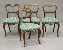 A set of four mid-Victorian rosewood framed spoon back dining chairs with carved centre rails and
