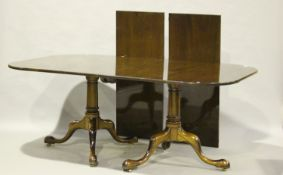A late 20th century George III style mahogany twin-pedestal dining table, the top with two extra