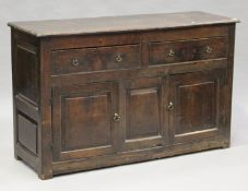 A George III oak dresser base, fitted with two frieze drawers above cupboards, on stile supports,