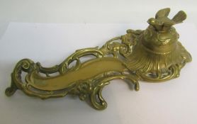 A late Victorian cast brass ink stand with single well under a domed cover with bird finial, with