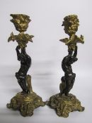 A pair of late 19c gilt and patinated bronze candlesticks with putti columns supporting the socles