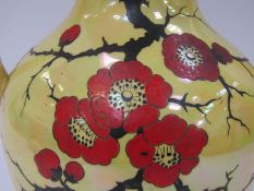 An Arcadian Stoke-on-Trent twin handled vase with lustre glaze, handpainted floral detail,