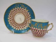 A Sevres 19th Century twin handled cup with saucer, with peacock decoration,