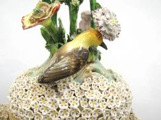 A pair of late 19th Century highly ornate lidded vases encrusted with flowers and birds,