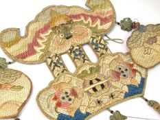 A selection of Oriental textiles including children's shoes, purse, and decorative adornments,