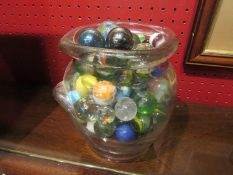 A glass jar containing a good quantity of marbles