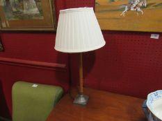 A mahogany and metal table lamp with cream shade