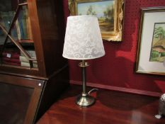 A bronzed metal table lamp with cream shade