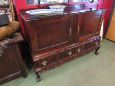 An early to mid 20th Century Dutch style sideboard with two doors over two drawers,