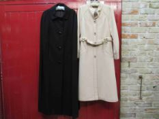 A 1970's Dorothy Rose black tailored wool full length cape and a Baccarat cream wool coat with belt,