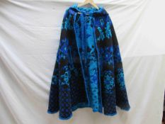 A late 1970's wool floral cape in tones of turquoise, blue and black,