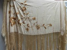 A cream silk shawl with fringing with embroidered golden flowers
