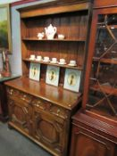 An oak dresser with plate rack back, two drawer on two cupboard door base,