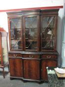 An astragal glazed top over three drawer three door cupboard base bookcase,