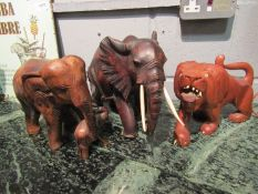 Two hardwood carved elephants and a lion