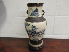 A Chinese vase with warriors on horseback, character marks to base, on carved hardwood stand,