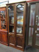A modern oak effect slim glazed cupboard on two door base,
