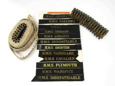 A collection of 12 Royal Navy cap tallies and two belts of inert .303 rounds.