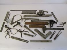 A box of measuring and marking tools including wooden and steel rukes, scribers, squares, calipers,