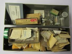 Five metal drawers of various watch parts and spares, mixed calibres, mainly stems, hands, crowns,