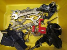 Four bench vices and mixed spanners