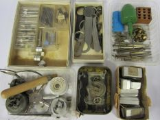 A box of mixed tools including movement holders, screwdrivers, spanners, balance stake, dust blower,
