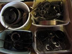 A box containing a large quantity of clock mainsprings, some unused,