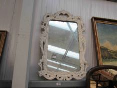 An ornate painted resin framed wall mirror