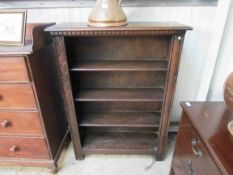 An oak bookcase with carved top and sides,