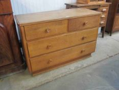A 1950's oak two over two chest of drawers
