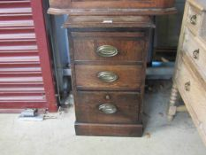 An oak pedestal chest of three drawers with pull-out slide,