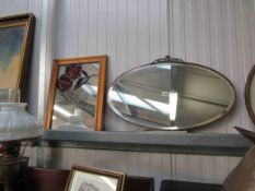 An Art Deco copper framed oval wall mirror and a pine framed mirror with coloured lead roses