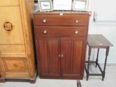 A 1940's utility mahogany tall boy with two drawers over two cupboard doors