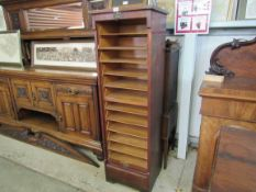 An Edwardian oak tambour roll front filling unit with twelve interior trays, no key,
