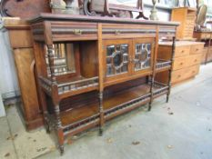 A Jas Shoolbred & Co 19th Century rosewood sideboard with two bevelled glass doors and spindle rail
