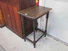 A 1930's oak barley twist lamp table