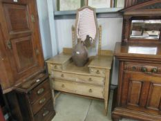 A 1930s stripped oak dressing table with mirror back and four drawers