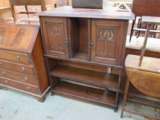 An Art Nouveau oak cupboard bookcase with two carved doors