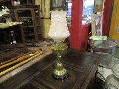 A Victorian oil lamp with brass base with foliate detail, half fluted brass reservoir,